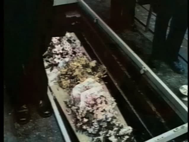 Medium shot of coffin lowered into grave