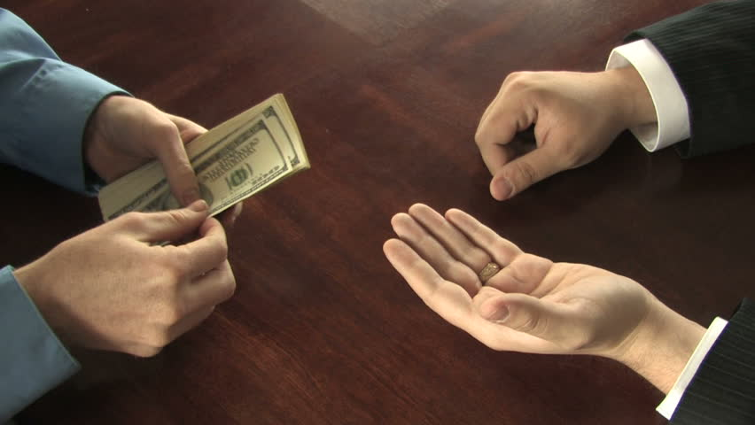 A man pays another man every last bill from a stack of hundreds in his hands