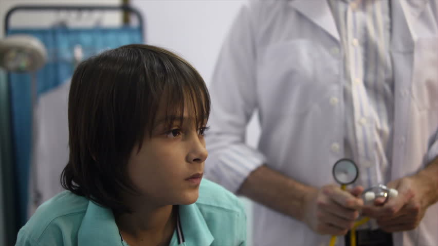 Friendly doctor at work and visiting with stethoscope sick child coughing in private medical clinic. Rack focus - HD stock footage clip