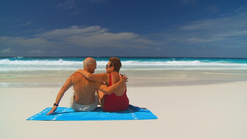 elderly couple sitting on beachtowel and relaxing on the beach - HD stock footage clip