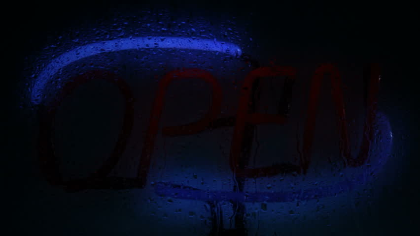 A glowing neon open sign seen through a rain splattered window, with flickering start up