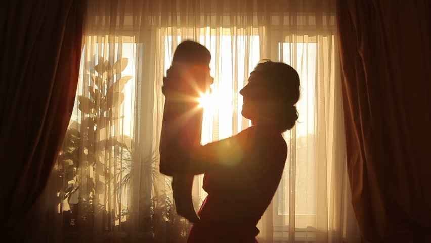 Mother plays with baby before window in silhouette
