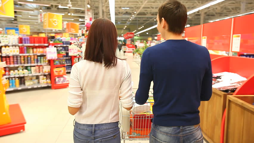 Couple walking through shopping mall with a market cart