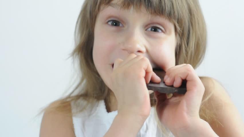 close-up portrait of a little girl eating chocolate - HD stock footage clip