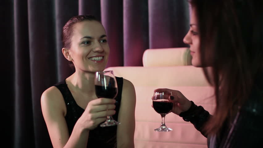 Two young women in a night bar with glasses of red wine  - HD stock footage clip