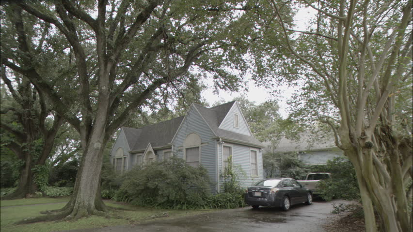Day Wide Low Angle Static Wet ground right quaint one story blue wood clapboard house white trim garage rear Blue car sedan light brown pick up truck parked driveway Lush green trees bushes Spr