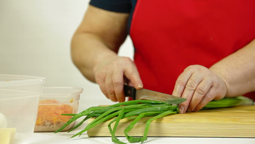 Mature woman chopping bunching onion for the cod-liver salad