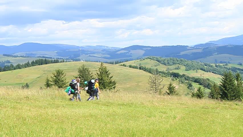 Hikers walking through ameadow