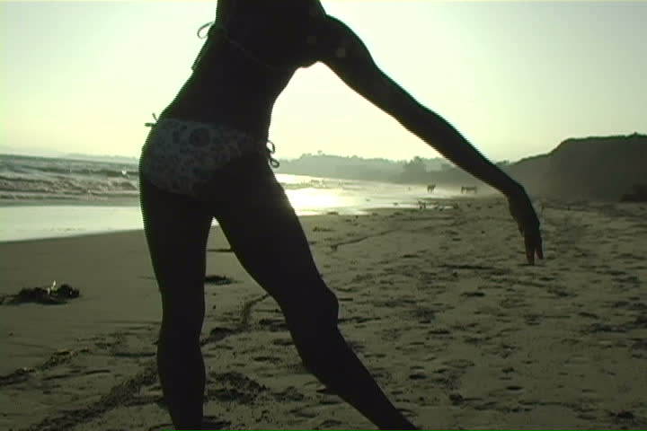 A beautiful, silhouetted young woman performs on the beach.   - SD stock footage clip