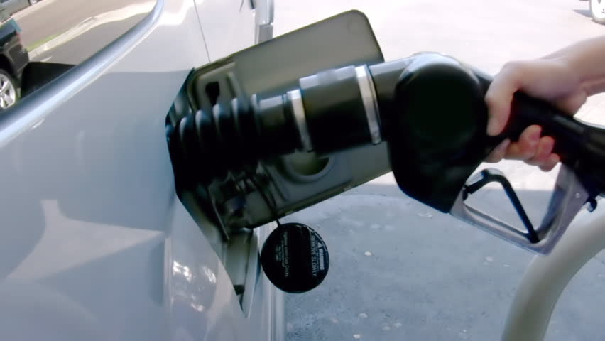 Pumping Gasoline Car (HD). Woman opens gas tank and loads the pump nozzle firmly. Logos and company IDs from nozzle and pump have been rotoscoped out frame by frame.