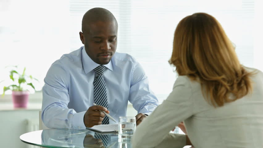 Young African-American man looking through the contract and asking his partner to clarify some clauses