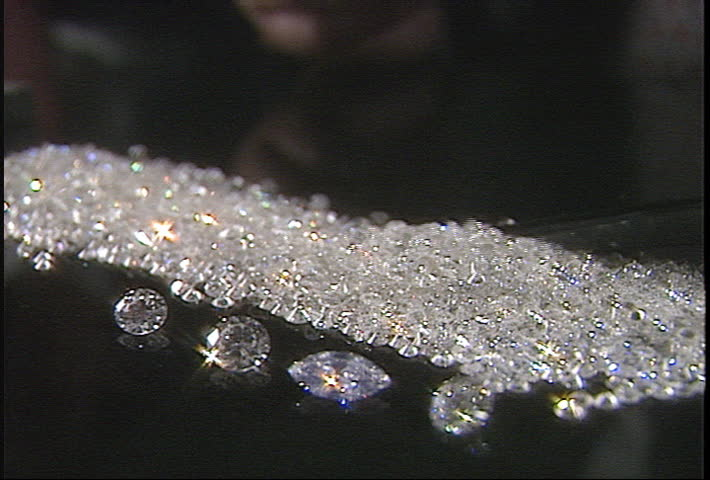 Jeweler combs through pile of diamonds and selects one