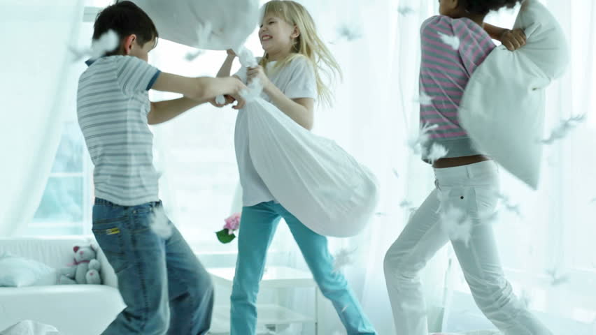 Kids pillow fighting so hard that feathers are falling all around them - HD stock video clip