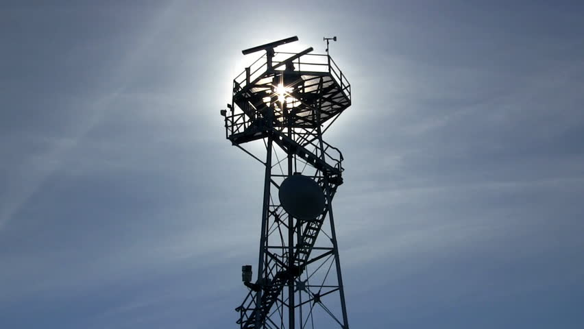 Marine traffic control radar tower silhouette with spinning antenna against blue sky and wispy clouds  - HD stock footage clip
