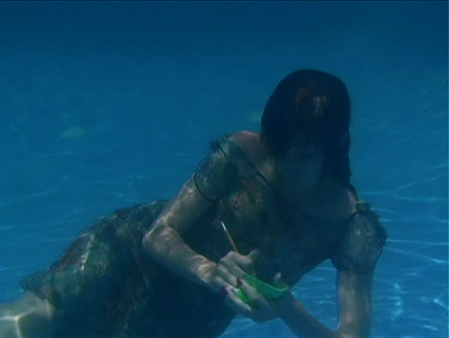 A beautiful brunette wearing a dress takes notes underwater.  Slow motion - 50%. - SD stock video clip