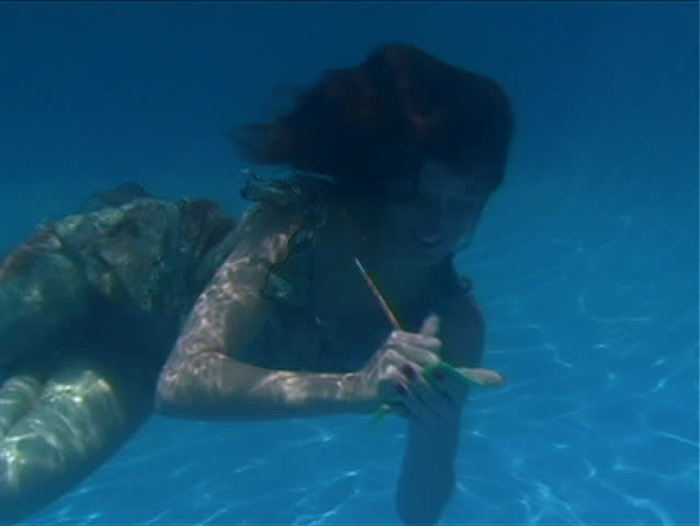 A beautiful brunette in a dress takes notes underwater.  Slow motion - 50% - SD stock footage clip