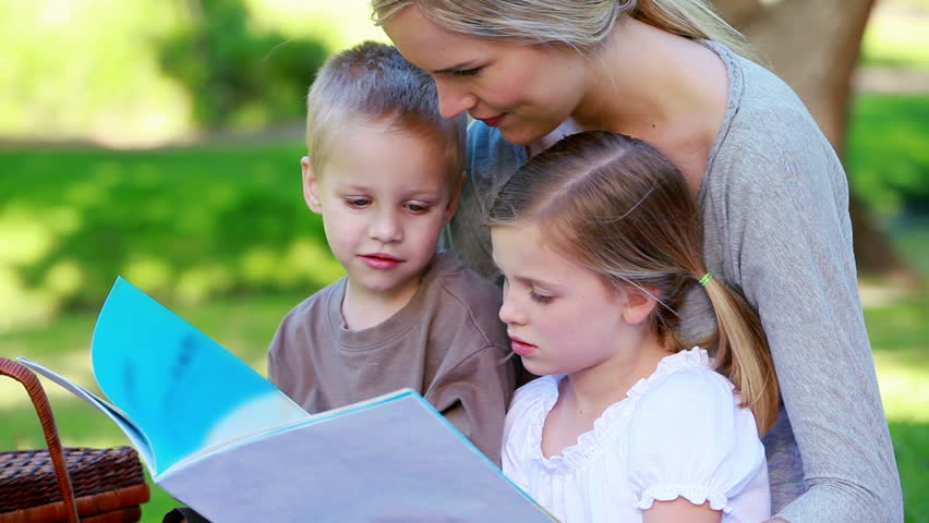 Children looking a picture book with their mother in a park - HD stock footage clip