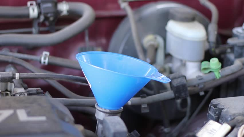 A close up of motor oil being poured into a funnel.