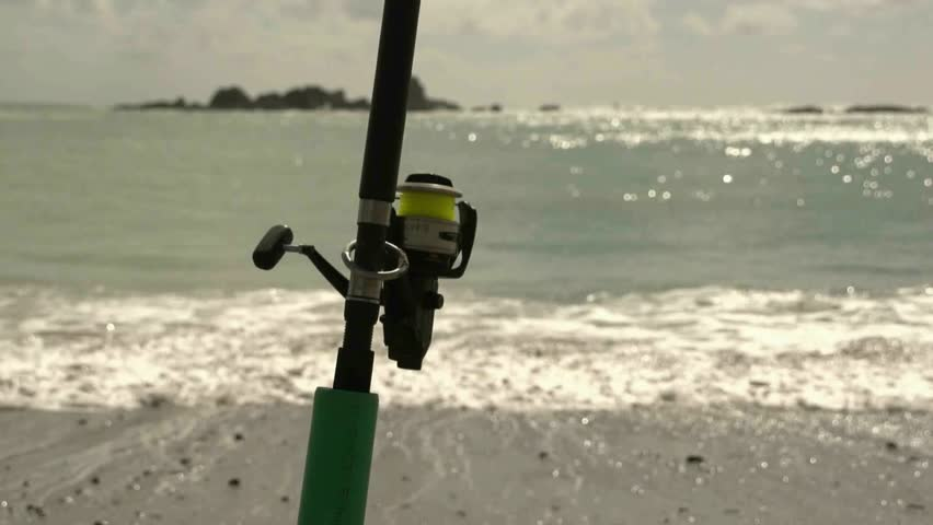 Fishing rod on the beach sitting in rod holder waiting for for Fish bite rod holders