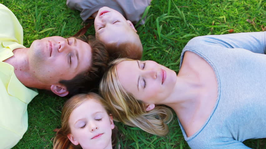 Family lying on the grass together - HD stock footage clip