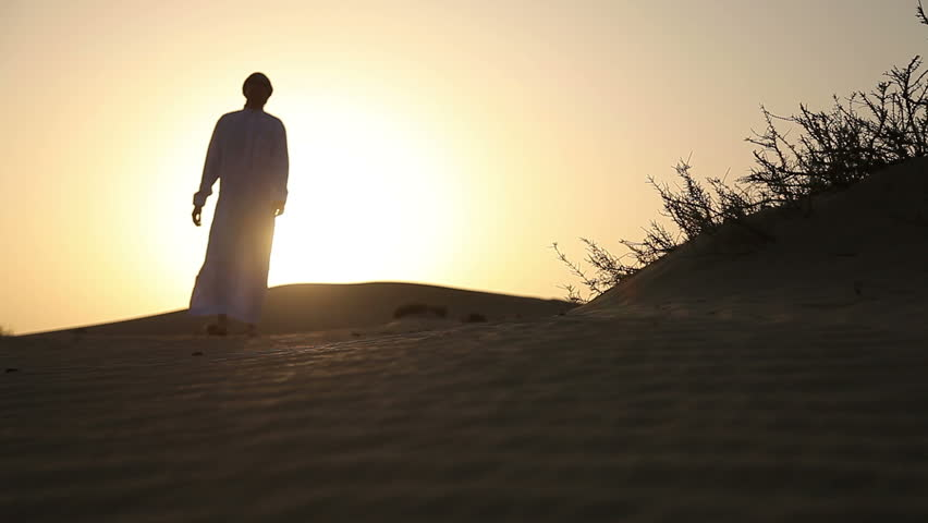 Weary man goes in the desert at sunset - HD stock footage clip