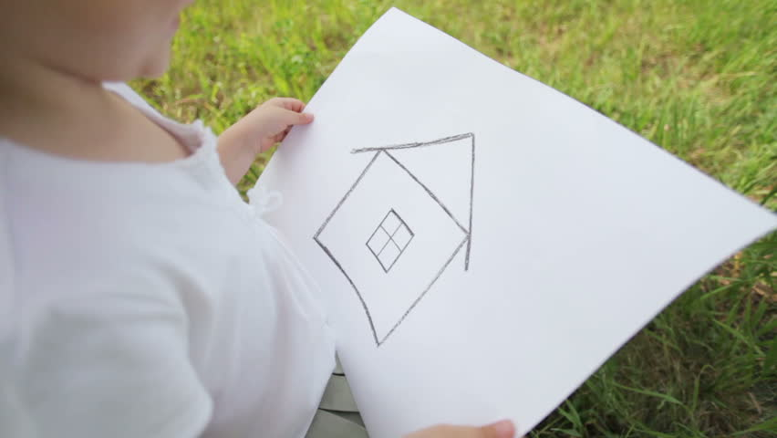 Girl on the field in construction helmet with a picture of a house.