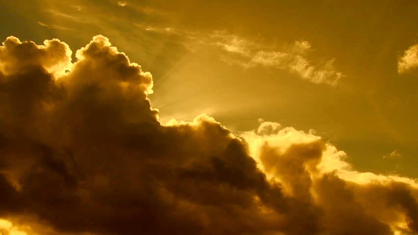 Beautiful cloudscape with large, building clouds and sunset behind shining sun rays and eventually breaking through cloud mass. Full HD 1920 x 1080.