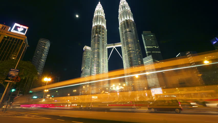KUALA LUMPUR - MAY 3: Timelapse in motion view of traffic and pedestrians near The Petronas Towers on May 3, 2012 in Kuala Lumpur, Malaysia.