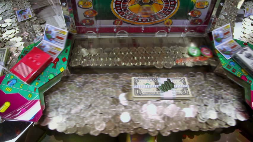 Play machine with many coins and dollars inside, closeup view - HD stock video clip