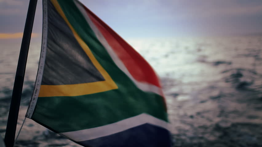 The South African flag blowing in the wind on a traveling motor boat in Cape Town, South Africa.