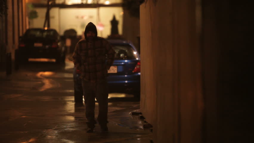 Homeless man walking down an alley on a cold rainy night