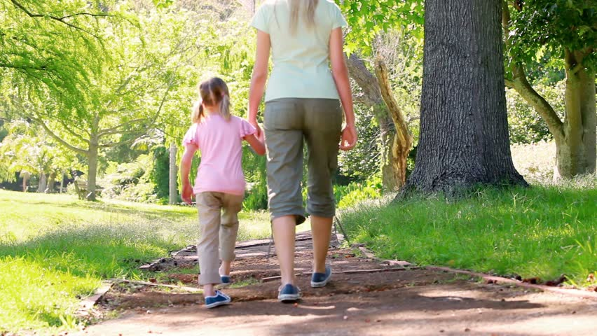 Mother and daughter walking together in a park - HD stock footage clip