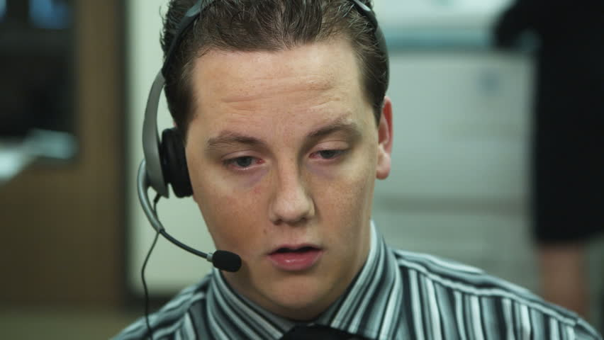 close-up: freckled office worker wearing headset stares vacantly with gaping mouth - HD stock video clip