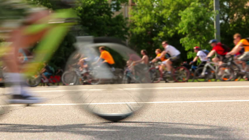 Many unrecognizable people ride on bicycles  (tilt-shift)