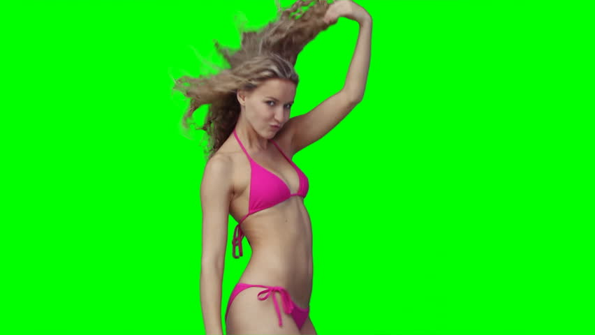 A dancing woman in a bikini against a green background - HD stock video clip