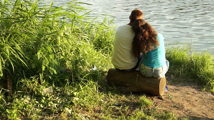 Loving couple sitting on a log near the water - HD stock footage clip