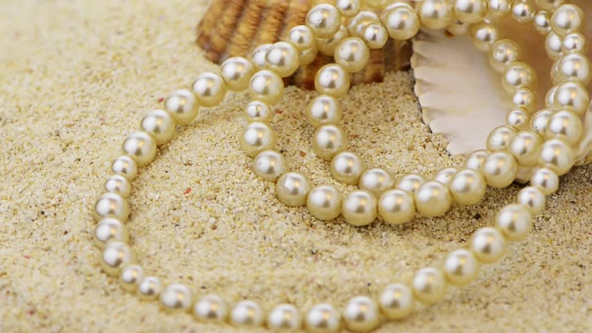 Pearls necklace on beach sand with shells rotating.