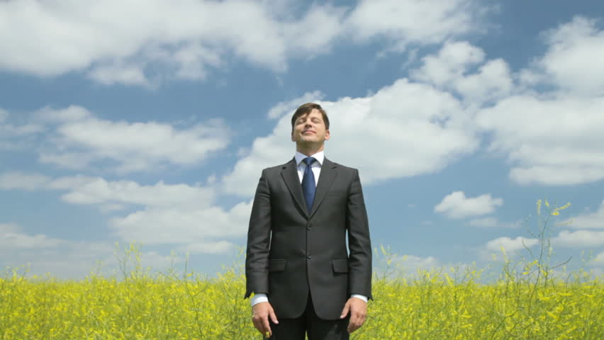 Young businessman standing in the field with his eyes shut enjoying trouble-free life