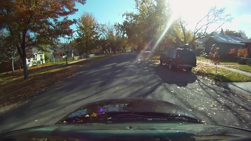 Car with roof-mounted camera drives through a residential neighborhood in autumn.