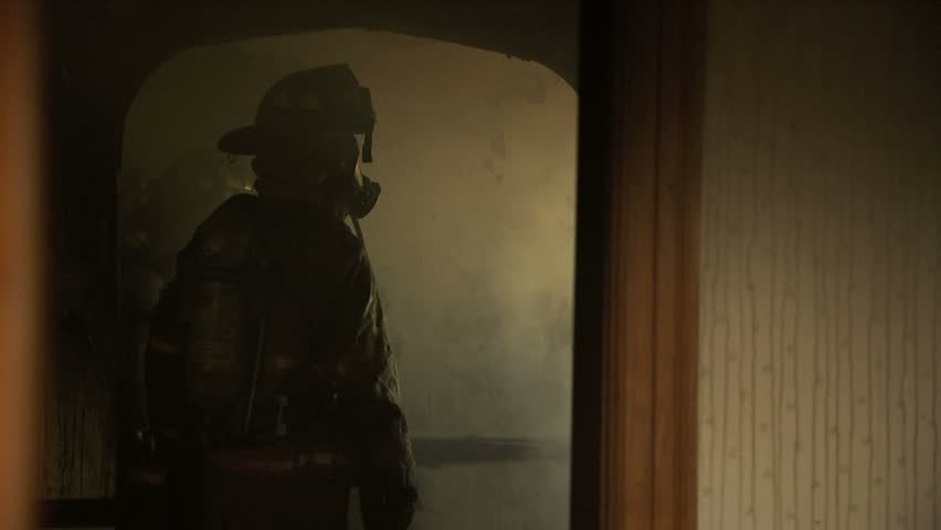Inside of house on fire with flames, smoke, and firemen