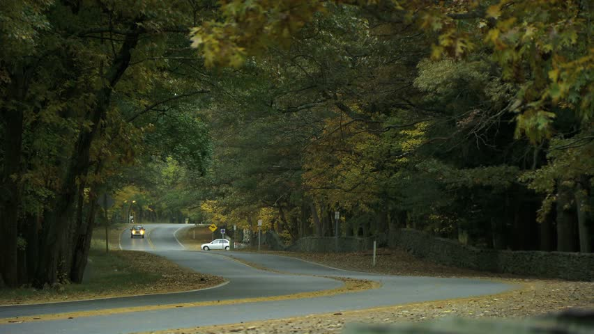 NEW ENGLAND - CIRCA NOVEMBER 2009: United States Postal Service delivery truck passing camera on country road