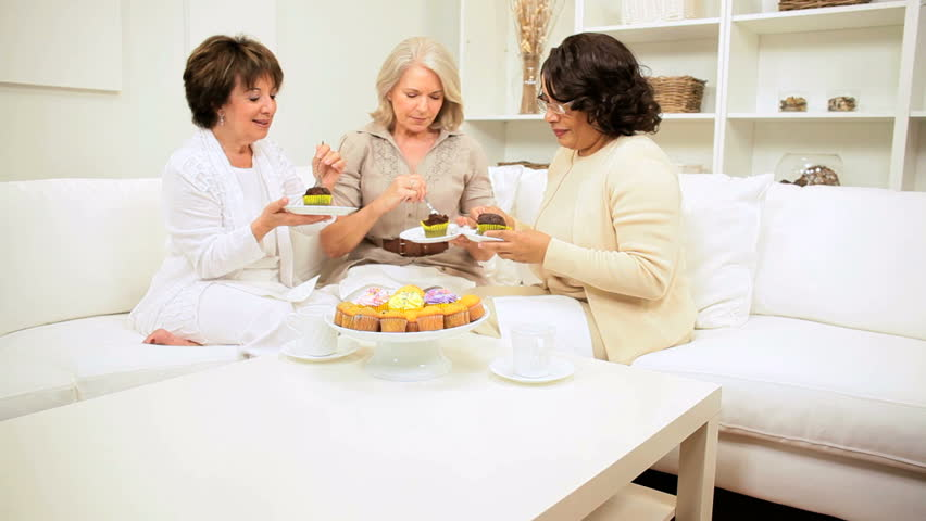 Multi ethnic senior lady friends visit drinking tea enjoying tempting cakes home - HD stock footage clip