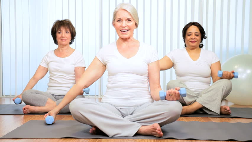 Older female instructor with mature members yoga fitness class - HD stock footage clip