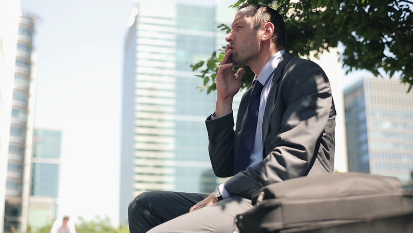 Businessman relaxing and smoking cigarette in the city
