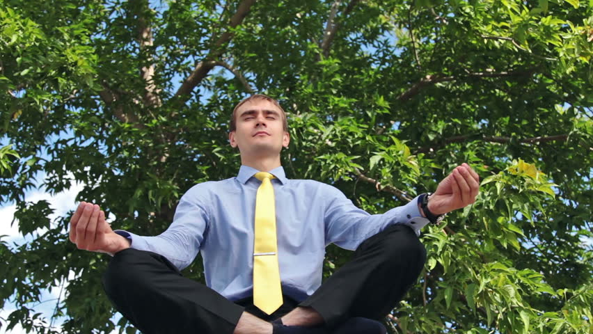 Young businessman doing yoga in the park - HD stock video clip