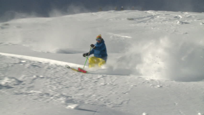 Skiing fast down a steep pitch in cold dry powder. Backlit snow highlights dry, cold, fluffy,  snow quality as skier passes camera.