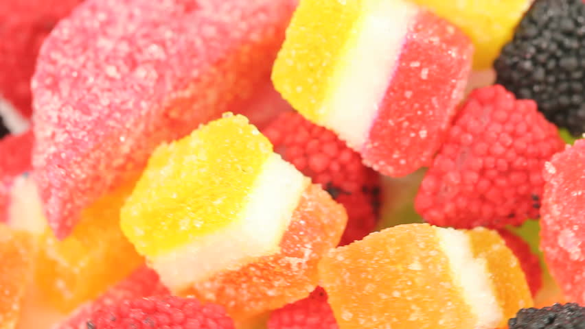 Colorful Jelly Cubes Background - Jelly cubes and berry jelly candy passing by in a loopable video, shot close up, vibrant color background