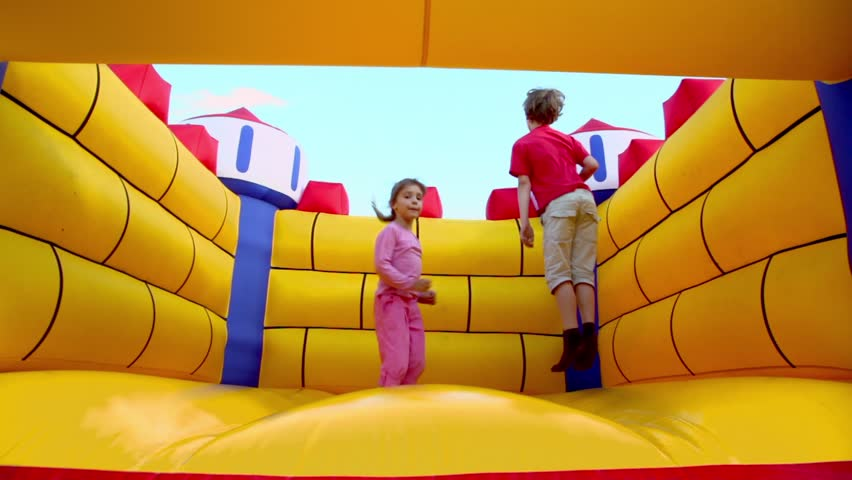 Two kids boy and little girl jump at inflatable playground at sunny summer day - HD stock footage clip