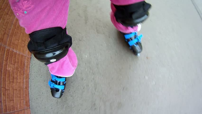 Little girl rollerblading on paved road near brick wall