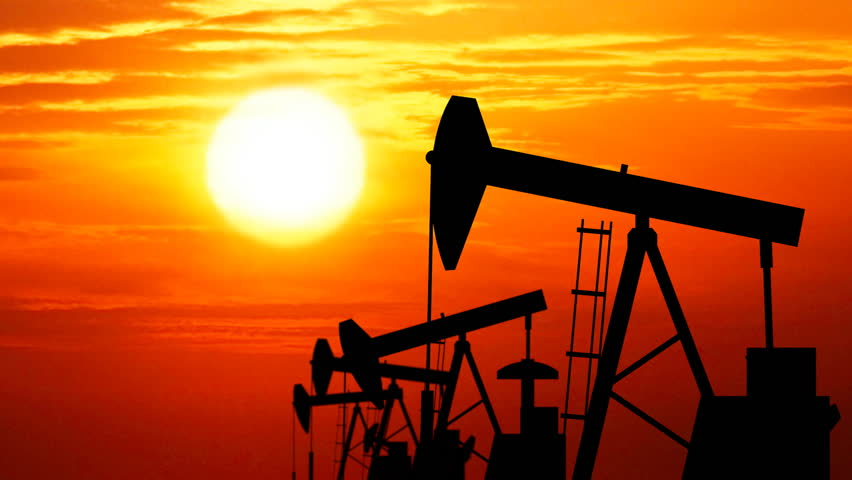 Silhouettes of oil pumps working. Seamless loop. Sun rays in the background. - HD stock video clip